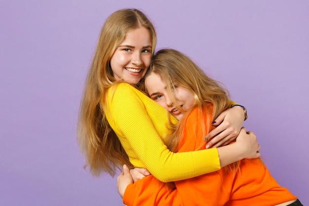 Due giovani sorelle gemelle bionde attraenti ragazze in abiti colorati vividi che si abbracciano, isolate sulla parete blu viola pastello. concetto di stile di vita familiare di persone.