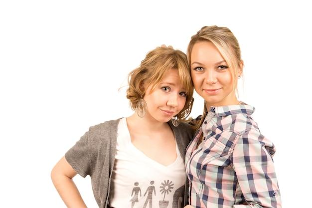 Due attraenti giovane donna bionda in abbigliamento casual in piedi vicino insieme, testa e spalle portait isolato su bianco