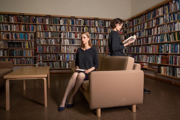 Due giovani studentesse attraenti che leggono libri nella biblioteca.