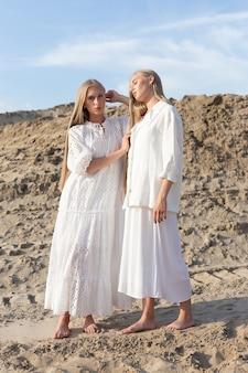 Due giovani sorelle gemelle attraenti che posano alla cava di sabbia in eleganti abiti bianchi