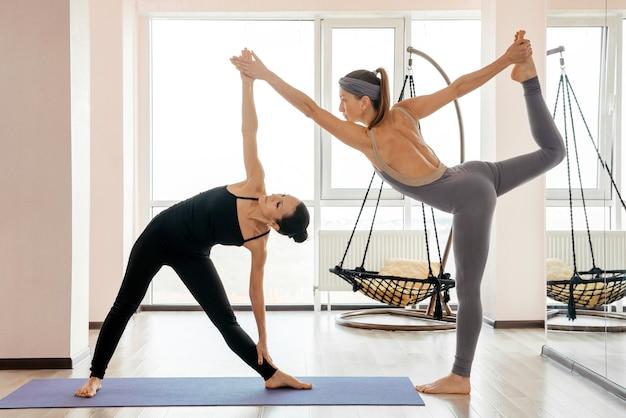 Due giovani donne attraenti che bilanciano e praticano lo yoga in uno studio di luce. benessere, concetto di benessere. foto di alta qualità
