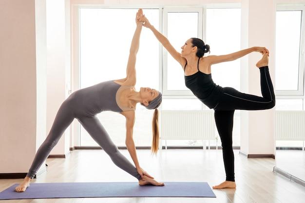 Due giovani donne attraenti che bilanciano e praticano lo yoga in uno studio di luce. benessere, benessere