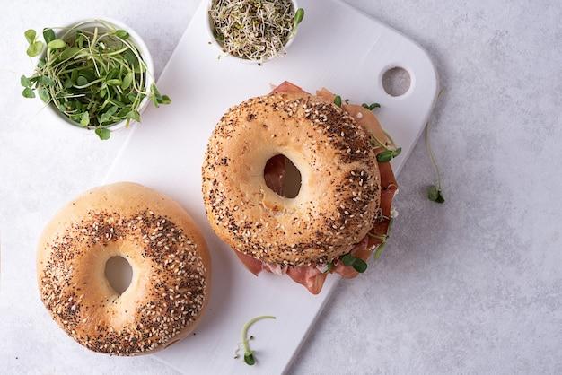Due bagel e una ciotola con microgreens su un tagliere, panini su uno sfondo bianco.