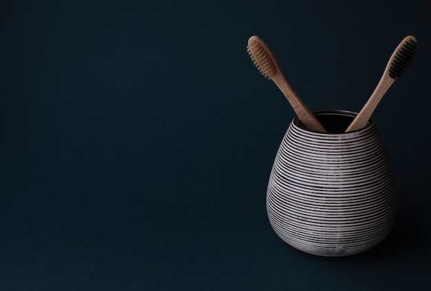 Due spazzolini da denti di bambù in un bicchiere di porcellana su uno sfondo sfumato ciano