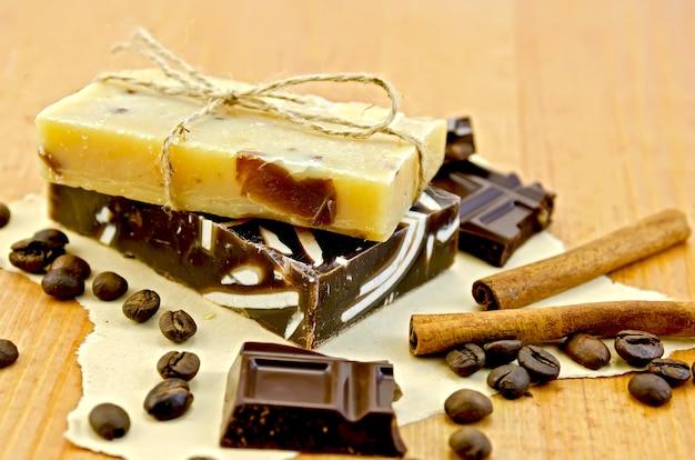 Due barre di sapone fatto in casa, legate con spago, cioccolato, cannella, chicchi di caffè su carta vecchia sullo sfondo di tavole di legno