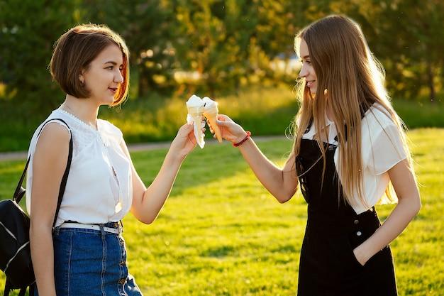 Due bellissime studentesse delle migliori amiche (studenti) che mangiano il gelato in un corno di cialda nel parco