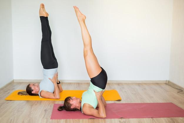 Due belle donne adulte che fanno yoga a casa