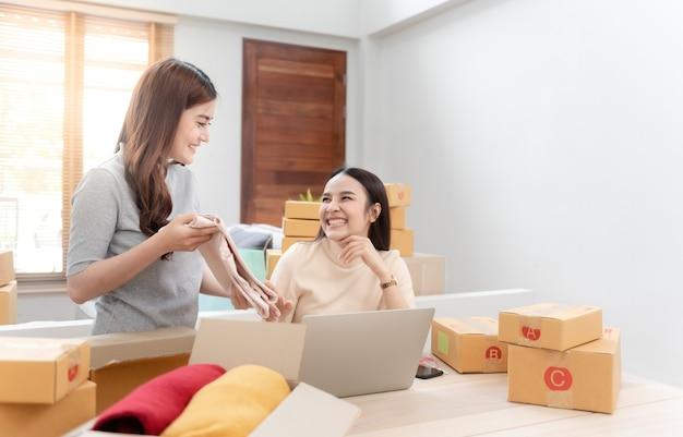 Due belle donne asiatiche controllano gli ordini dai laptop tramite internet. e imballare la scatola di carta con una faccia sorridente felice, essendo un nuovo normale business online