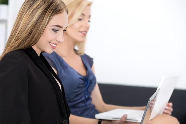 Due belle donne d'affari seduti al seminario e scrivendo qualcosa. formazione aziendale e concetto di successo