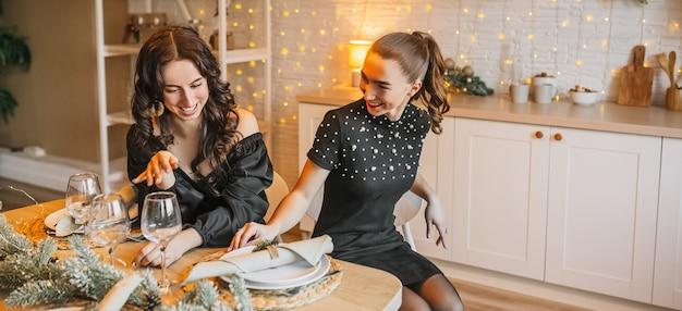 Amico di due belle ragazze felici allegre che ride al tavolo da pranzo di natale sullo sfondo della cucina di capodanno