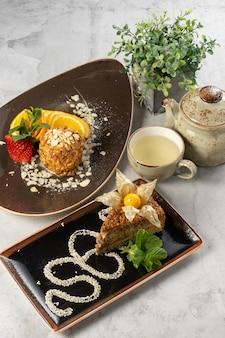 Due bei dessert e una tazza di tè verde con un bollitore. gelato fritto con fragole fresche e torta all'arancia e esterhazy con physalis e menta