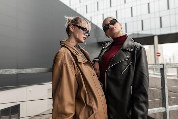 Due belle ragazze alla moda con occhiali da sole in un'elegante giacca di pelle in posa per strada in città
