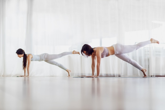 Due belle ragazze magre in forma che fanno yoga in studio di yoga. sono in posizione one legged plank.