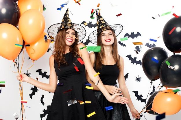 Due belle ragazze in abiti neri e cappelli da strega si divertono con palloncini e coriandoli neri e arancioni. festa di halloween .