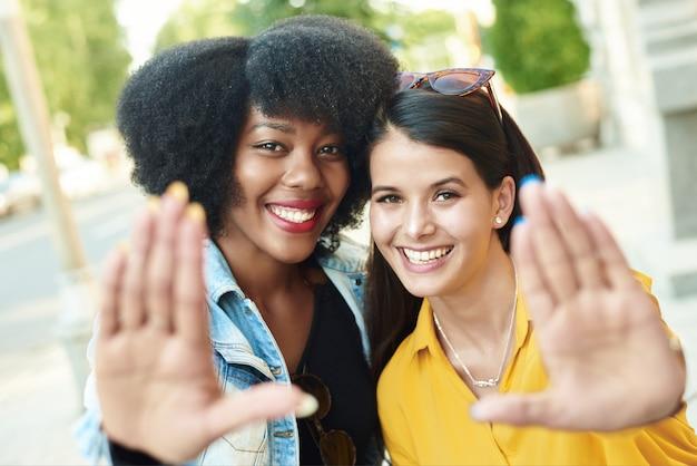 Due belle ragazze di diverse nazionalità mostrano la cornice con le mani e sorridono a