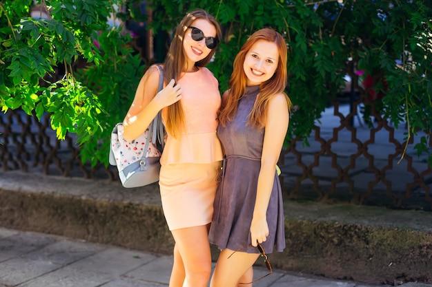Due belle ragazze in abiti stanno sullo sfondo di un albero e di una recinzione