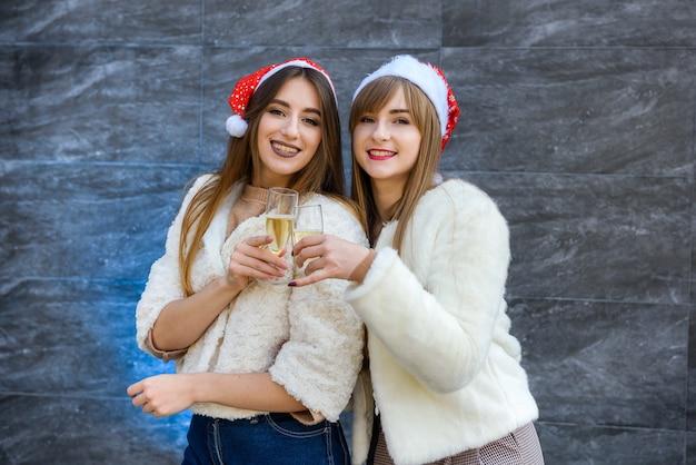 Due belle ragazze in giacche di pelliccia e champagne che festeggiano il nuovo anno