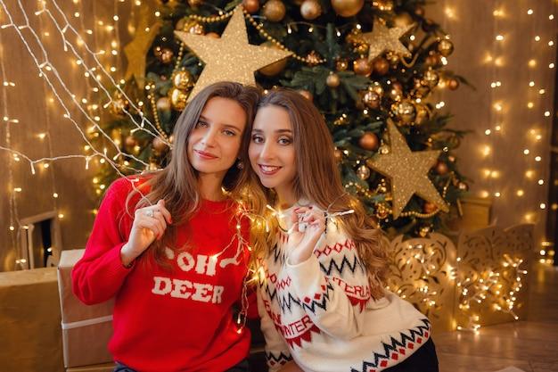 Due belle ragazze alla vigilia di capodanno. migliori amiche della giovane donna che celebrano il natale in casa. l'amicizia di divertimento non finisce mai il concetto. bellissime decorazioni natalizie dorate su un alto albero di natale