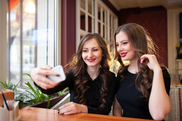 Due belle ragazze fanno selfi e bevono caffè