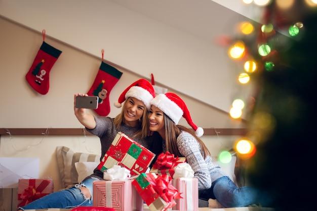 Due belle ragazze che si siedono sul letto con il mazzo sui regali davanti loro.