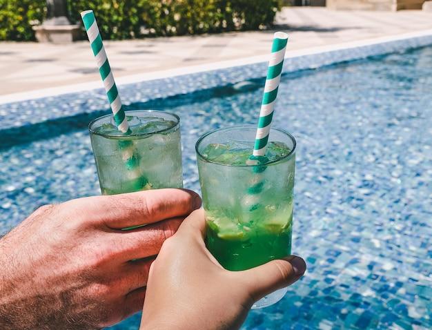 Due bei bicchieri con un rinfrescante cocktail sullo sfondo della piscina. vista dall'alto, primo piano. concetto di vacanza e viaggio. momenti di festa