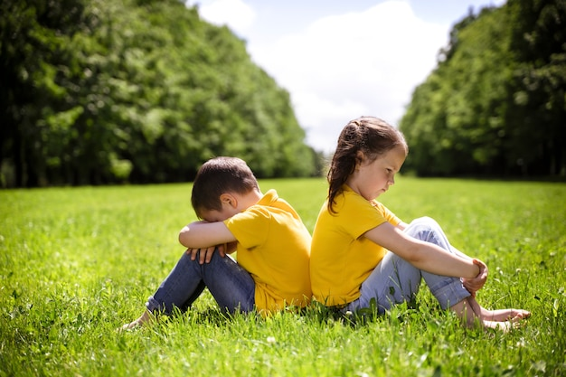 Due bei bambini in buona salute in magliette gialle si siedono sull'erba verde