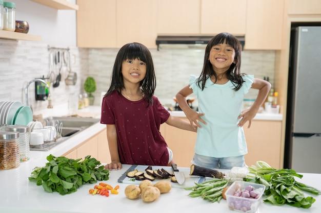 Due bella bambina che prepara e cucina insieme la cena in cucina