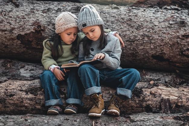 Due belle bambine che leggono libri nella foresta autunnale, sedute su un tronco. il concetto di educazione e amicizia.
