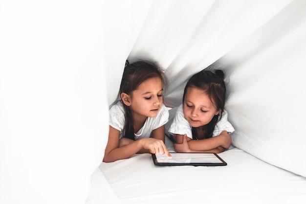 Due bellissime sorelline sdraiate nel letto e guardare lo schermo di un tablet, bambini intelligenti che utilizzano la tecnologia intelligente