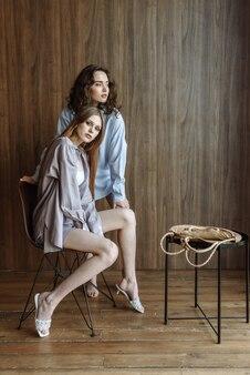 Due bellissime donne modello in posa in studio con nuovi vestiti alla moda