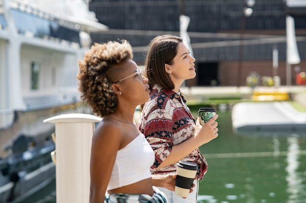 Due belle donne multirazziali, che passeggiano per il porto con un caffè, barche e yacht sullo sfondo