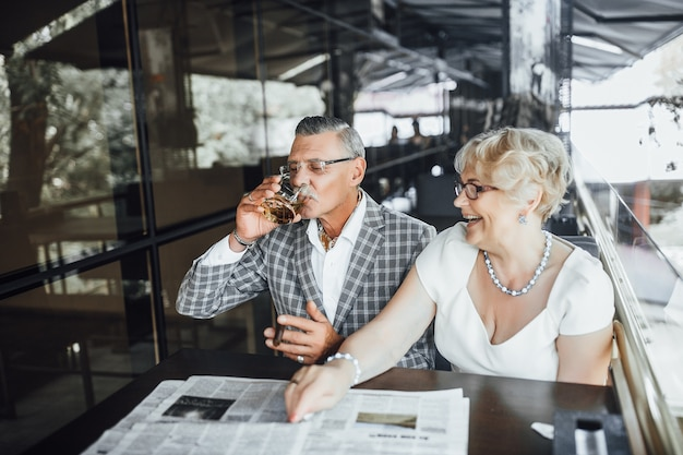 Due bellissime coppie di anziani bevono vino sulla terrazza estiva e leggono il giornale in questo momento