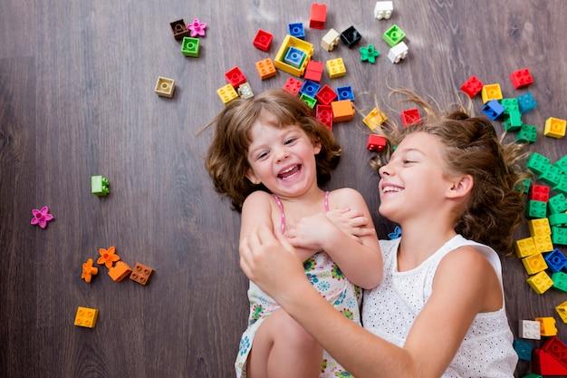 Due belle sorelle di pari livello che giocano con i blocchi giocattolo di costruzione. bambini che giocano il solletico.
