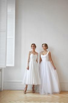 Due bella donna snella in abito da sposa bianco