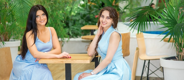 Due belle giovani donne caucasiche sorridenti in lunghi abiti blu seduti al tavolo e guardando la telecamera in un caffè all'aperto