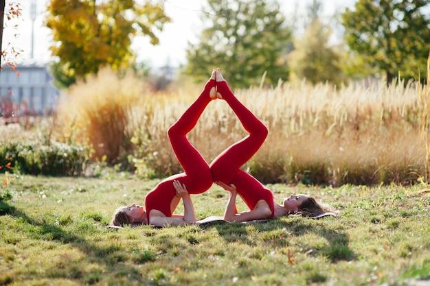 Due belle giovani donne in forma sportiva sedute in easy (pleasant posture), sukhasana, meditando con gli occhi chiusi, respirando, allenandosi all'aperto in estate, indossando canottiere rosse e blu abbigliamento sportivo