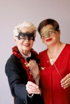 Due belle donne anziane mature alla moda in maschere di carnevale con scintillii che celebrano il nuovo anno