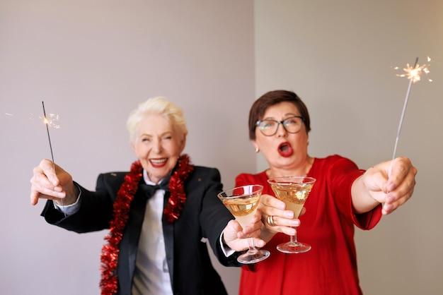 Due belle donne anziane mature alla moda che celebrano il nuovo anno