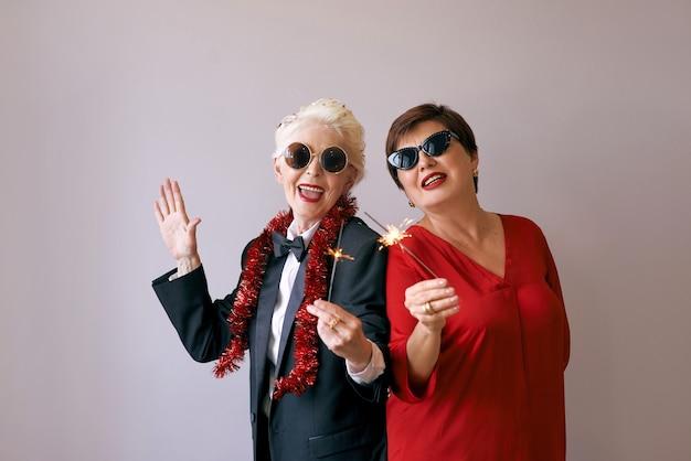 Due belle donne anziane mature alla moda in occhiali da sole che celebrano il nuovo anno