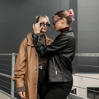 Due belle ragazze sorelle adolescenti in una giacca di pelle alla moda con jeans neri in città. la donna regola gli occhiali da sole di un'altra donna.