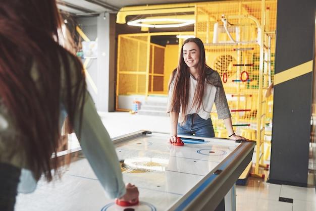Due belle gemelle giocano a air hockey nella sala giochi e si divertono