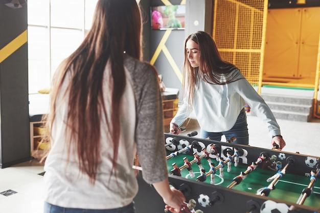 Due belle gemelle giocano a calcio balilla e si divertono. una delle sorelle tiene in mano una palla giocattolo e mostra la lingua