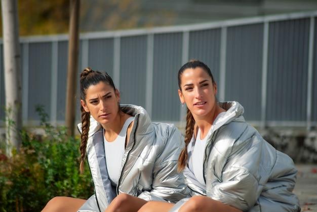 Due belle sorelle gemelle in giacche grigie