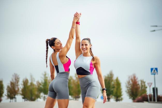 Due bellissime sorelle gemelle che corrono per la città in abiti sportivi
