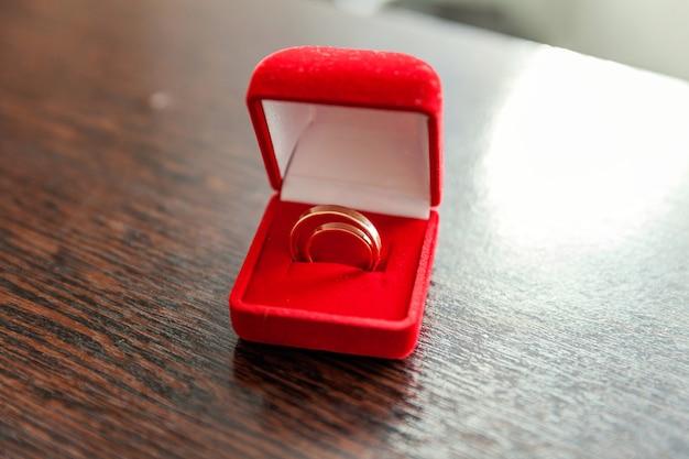 Due bellissime fedi nuziali su portagioie rosso su sfondo chiaro. dichiarazione d'amore biglietto di nozze saluto di san valentino