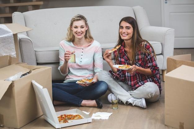 Bella donna due che mangia pizza nella nuova casa