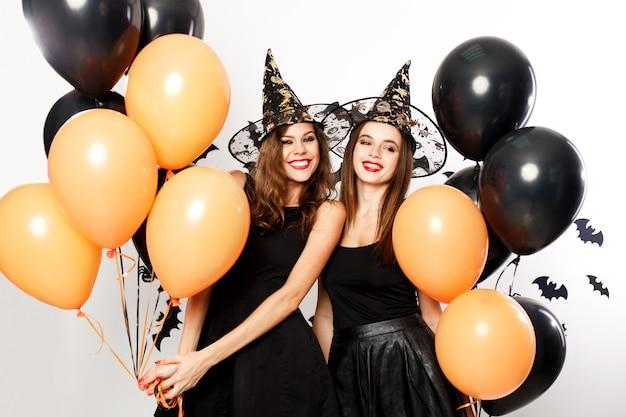 Due belle donne in abiti neri e cappelli da strega si divertono con palloncini neri e arancioni. festa di halloween .
