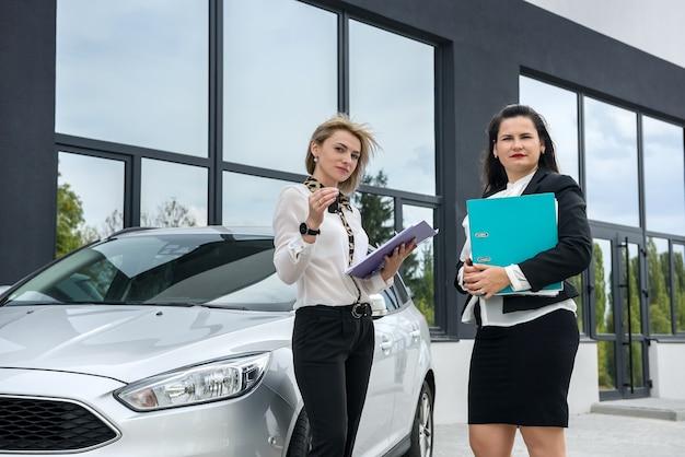 Due belle donne che si stringono la mano vicino alla nuova auto in piedi fuori e sorridono