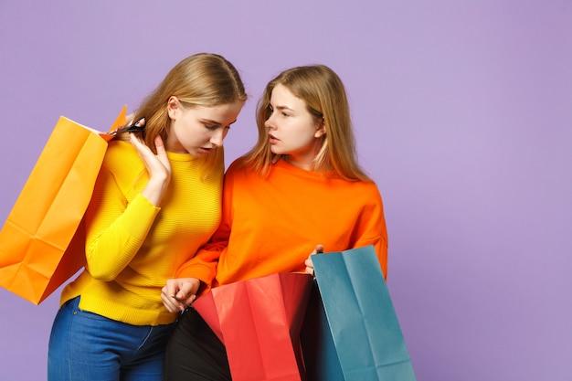 Due belle giovani sorelle gemelle bionde ragazze in abiti vivaci tengono il pacchetto con gli acquisti dopo lo shopping isolato sulla parete blu viola. concetto di stile di vita familiare di persone.