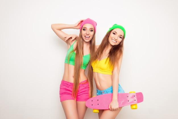 Due amiche belle e giovani che si divertono con uno skateboard